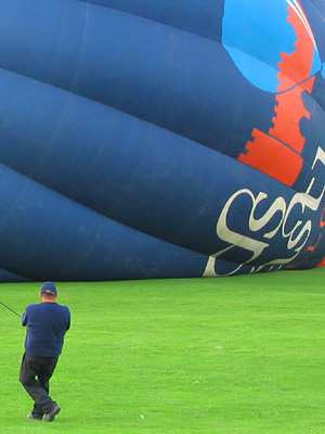 Crew man, crown line, hot air balloon, blue, inflating, launching, lawn, Leeds Castle, Kent, England, Britain, UK, May 2007